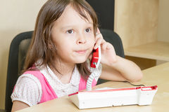 Young child on phone with pursed lips Stock Image