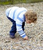 Young child picking up stones. Stock Image