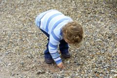 Young child picking up stones. Stock Images