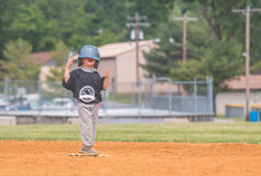 Young Child Playing Baseball. Little boy having fun and goofing around while playing baseball Stock Image