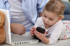 Child playing with  mobile phone. Young child playing with her father's mobile phone Royalty Free Stock Photography