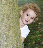 Young child playing hide and seek in the park, hiding behind a tree. Very pretty. Pretty young girl, toddler, playing hide and seek. She is peering round a tree Royalty Free Stock Image