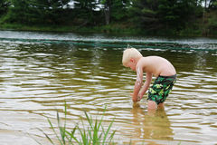 Young Child PLaying Outside in Lake Stock Photography