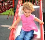 Young child playing on a slide at the playground. A young girl, toddler playing on a slide at the playground in the park. She has blonde curly hair and is Royalty Free Stock Images