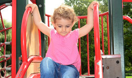 Young child playing on a slide at the playground. A young girl, toddler playing on a slide at the playground in the park. She has blonde curly hair and is Royalty Free Stock Photos