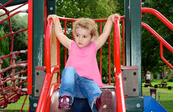 Young child playing on a slide at the playground. A young girl, toddler playing on a slide at the playground in the park. She has blonde curly hair and is Stock Photos