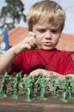 Young child playing soldiers Stock Photography