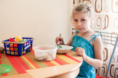 Young child plays with toys at table and eating Royalty Free Stock Image