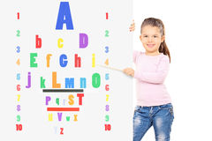 Young child pointing on colorful eyesight test with wooden stick. Young child pointing on a colorful eyesight test with a wooden stick isolated on white Stock Photos