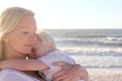 Young Child Protect Safely in Mother's Loving Embrace on Beach Stock Photo