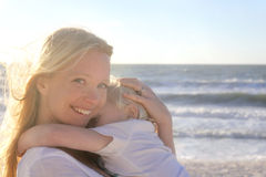 Young Child Protect Safely in Mother's Loving Embrace on Beach Stock Images