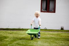 Young Child Pushing Wheelbarrow. A young child pushing a wheelbarrow outdoors in a rural farm setting Royalty Free Stock Image