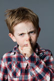 Young child with red hair and freckles frowning for silence Royalty Free Stock Photos