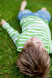 Young child relaxing on green grass Royalty Free Stock Photography