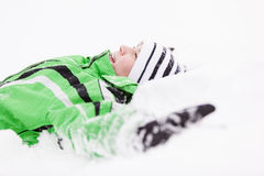 Young child relaxing lying on the fresh snow Royalty Free Stock Photos
