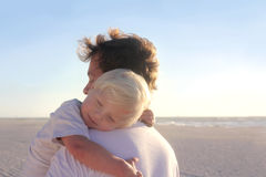 Young Child Resting in Father's Arms on Beach Stock Images