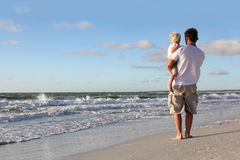 Young Child Resting in Father's Arms on Beach by Ocean Stock Photos