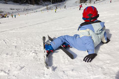Young Child rests on the edge of a ski slope. Ski resort:  Young Child rests on the edge of a ski slope Stock Photo