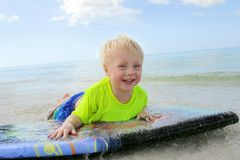 Young Child Riding on Boogie Board in Ocean Royalty Free Stock Images