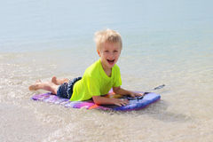 Young Child Riding on Boogie Board in Ocean Stock Images