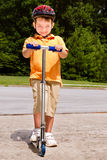 Young child riding scooter outdoors Royalty Free Stock Photography