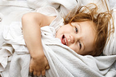 Young child rolling in white covers Stock Photography