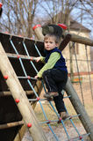 Young child on rope ladder. Portrait of young child playing in playground, climbing rope ladder Stock Images