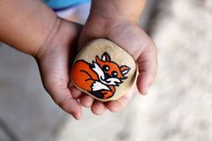 Young Child`s Hands Holding a Painted Rock with A Cartoon Fox on. A little 3 year old toddler child`s hands are gently holding a painted rock with a fox on it stock image