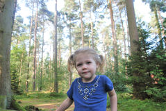 Young Child sat in front of tall trees Royalty Free Stock Photo