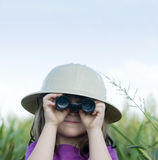 Young child searching with safari hat and binocula. Young child in countryside searching with safari hat and binoculars stock images
