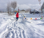 Young Child Shoveling Snow. Young boy shoveling a snow covered sidewalk. Christmas decorations in the shot Stock Photo