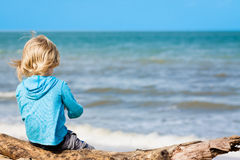 Young child sitting at the beach Stock Images