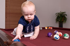 Young child sitting on a billiard table dropping a ball in a pocket. A young child sitting alone on a billiard table dropping a blue ball into a side pocket Stock Photo
