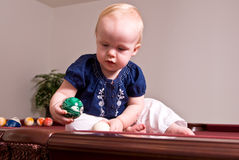 Young child sitting on a billiard table dropping a ball in a pocket. A young child sitting alone on a billiard table holding a green ball and looking into a side Royalty Free Stock Photo