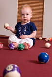 Young child sitting on a billiard table holding a cue ball. A young child sitting alone on a billiard table playing with the pool balls. She holds a cue ball in Royalty Free Stock Photos