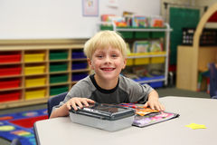 Young Child Sitting at Desk in Kindergarten CLassroom Royalty Free Stock Photos