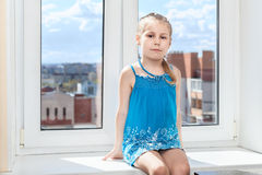 Young child sitting in middle of window Royalty Free Stock Photo
