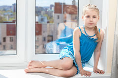 Young child sitting on window sill in sun light Stock Photos