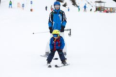 Young child, skiing on snow slope in ski resort in Austria. Young preschool child, followed by his father, skiing on snow slope in ski resort in Austria Royalty Free Stock Photos