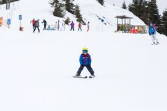 Young child, skiing on snow slope in ski resort in Austria Stock Images