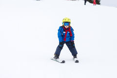Young child, skiing on snow slope in ski resort in Austria Stock Photo