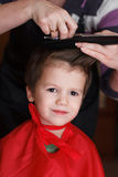 Young child with smile at the hairdresser having a haircut Stock Photo