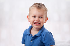 Young child smiling. Cute little blond boy smiling Royalty Free Stock Photo
