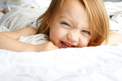 Young child smiling in white blankets Royalty Free Stock Photos