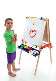 Young child standing at art easel Royalty Free Stock Photography