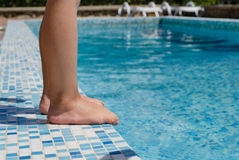 Young child standing at the edge of a pool Stock Images
