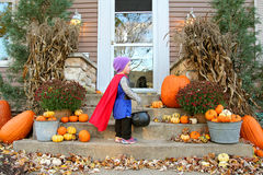 Young Child Standing at House Trick-or-Treating on Halloween. A young child dressed up in a costume like a knight with a cape is standing at a house waiting for Royalty Free Stock Image