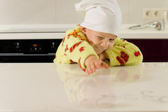 Young child stretching across a kitchen counter Stock Image