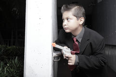 Young child in a suit with a gun Royalty Free Stock Photo