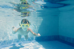 Young child swimming underwater in pool Royalty Free Stock Image